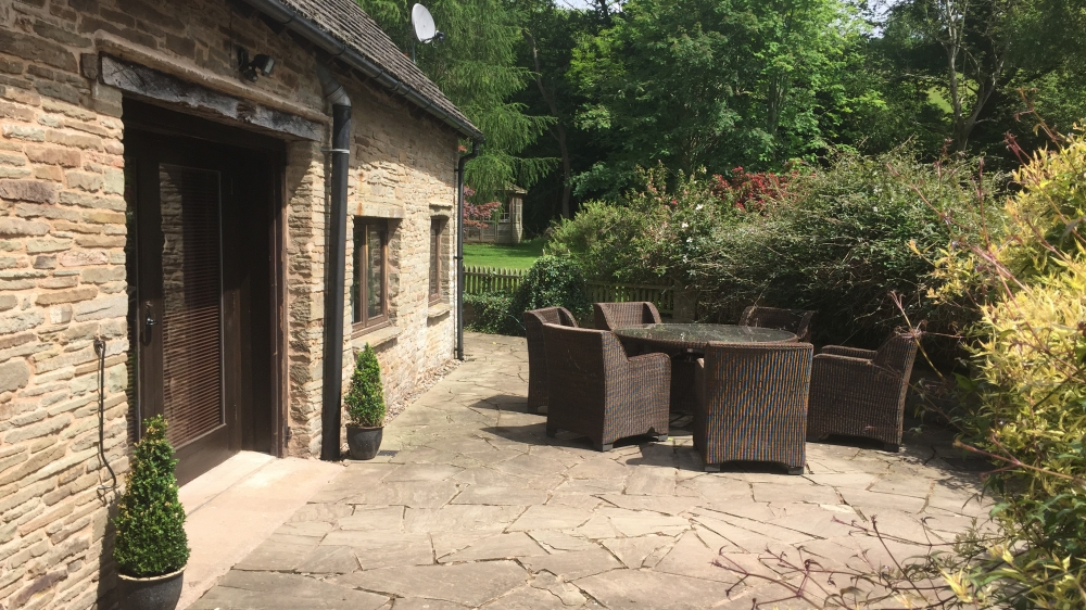 Forest Mill Cottage patio overlooking the River Monnow in the Brecon Beacons